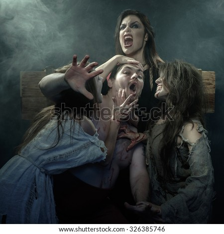 Halloween. The Middle Ages. Three evil witches kill his executioner - stock photo