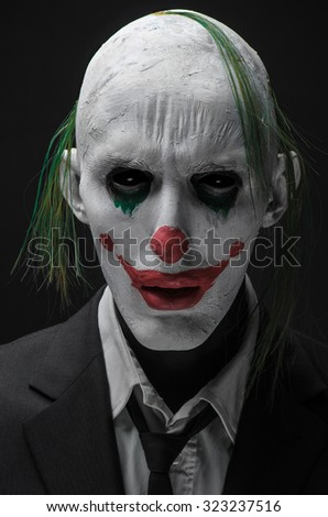 Halloween theme: Crazy terrible green clown in black suit isolated on a dark background in the studio
