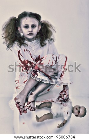 Halloween Theme: Girl Child Zombie or Ghost covered in blood holding baby doll. - stock photo