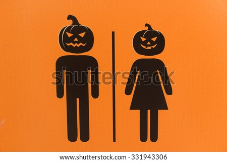 Halloween toilet sign, Male and female toilet sign on orange corrugated plastic. - stock photo