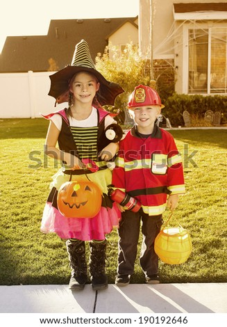 Halloween Trick-or-treaters at warm autumn sunset - stock photo