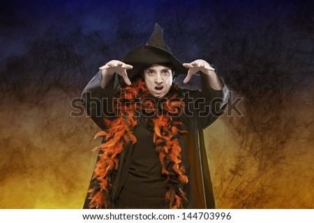 halloween witch casting a spell on dark background - stock photo