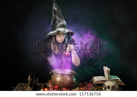 Halloween witch cooking a potion in a copper cauldron - stock photo