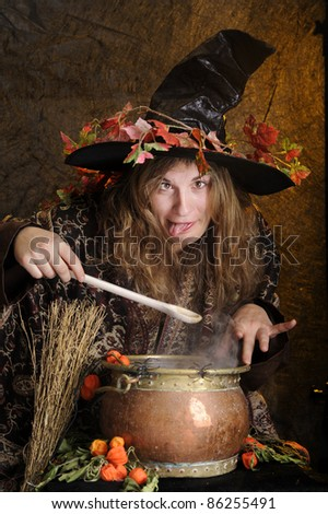halloween witch cooking in a copper, making faces - stock photo