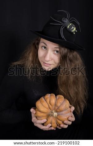 Halloween witch holding a pumpkin - stock photo