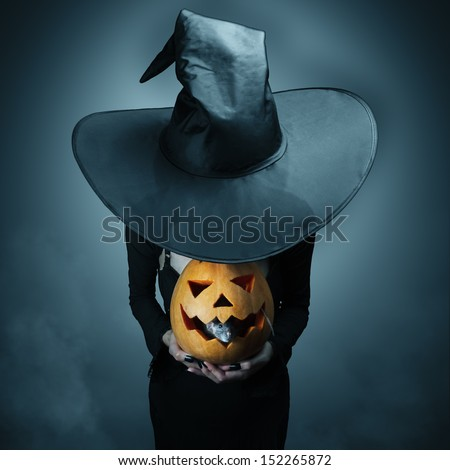 Halloween witch holding a pumpkin, which sits inside a rat