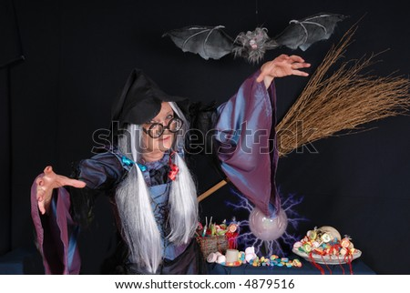 Halloween witch offering candy, sweets, trick or treat, holiday, happiness, food concept