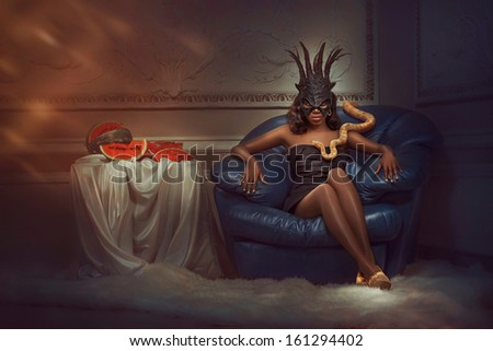 Halloween Witch sitting in a chair with snake - stock photo