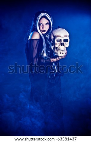 Halloween witch with a skull over black background with blue smoke - stock photo