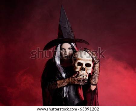 Halloween witch with a skull over black background with red smoke - stock photo