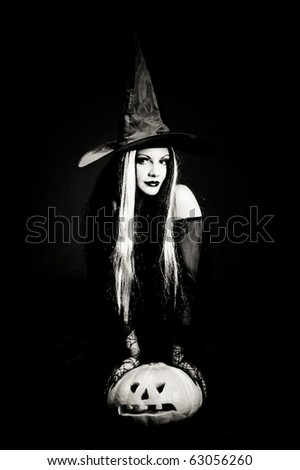 Halloween witch with a skull over black background with smoke - stock photo