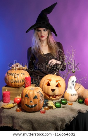 Halloween witch with pumpkins on color background