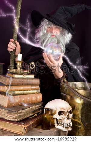 Halloween wizard looking into his glass sphere - stock photo