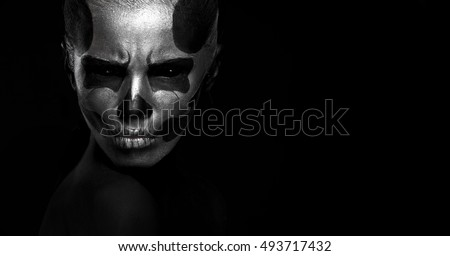 Halloween. Woman in day of the dead mask skull face art. Halloween face art on black background. Halloween make up.