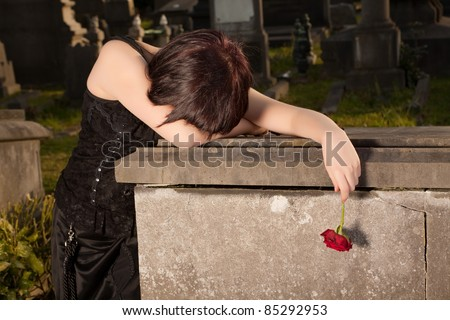Halloween woman in gothic dress crying on a tomb - stock photo