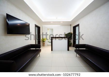 Hallway in the beauty salon with two black leather divans and big TV panel on the wall. - stock photo