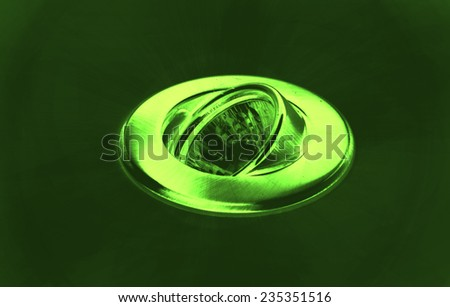 Halogen ceiling light on green background, abstract image - stock photo