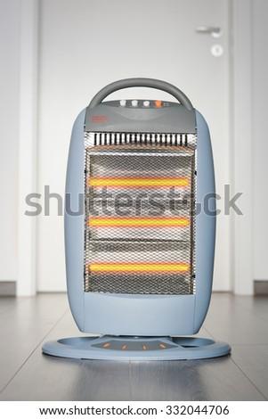 Halogen or infra heater in action against wooden floor - stock photo