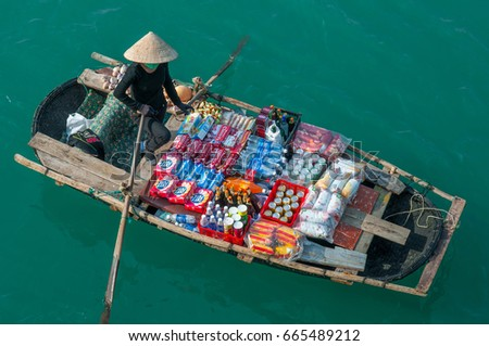 HALONG BAY, VIETNAM - NOVEMBER 23, 2009: Vietnamese saleswoman with conical hat and her goods rowing on the green emerald waters of Halong Bay in the South China Sea.