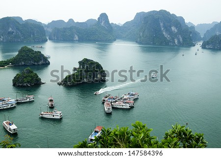 HALONG, VIETNAM - JUNE 22 : Tourist Junks in Halong Bay, Vietnam on June 22,2013. Ha Long Bay is a UNESCO World Heritage Site  - stock photo