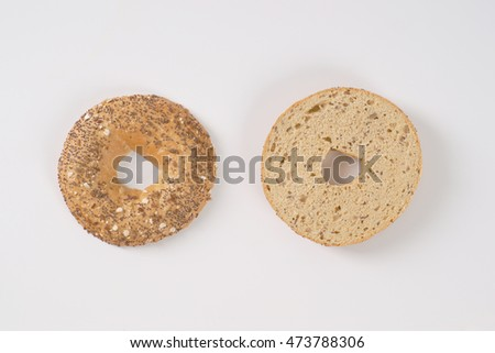 halved bagel with seeds on white background