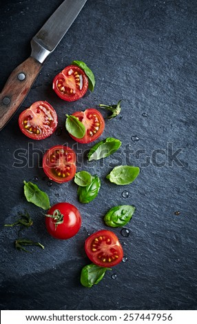 Halved cherry tomatoes and basil leaves on a black slate  - stock photo