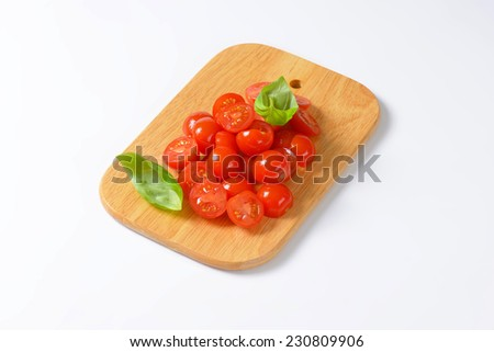 halved cherry tomatoes with basil served on the wooden cutting board - stock photo
