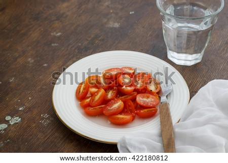 halved fresh ripe tomato salad showing the pips with salt served in white plate put  on a dark rustic table, healthy food project, vegan food - stock photo