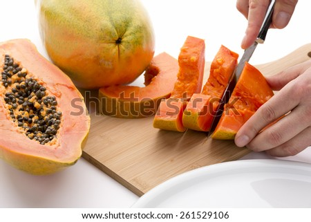 Halved papaya fruit being cut into slices with a sharp kitchen knife on a wooden cutting board. Half a pawpaw fruit and an entire papaya placed next to it. Orange colored fruit pulp. White background. - stock photo