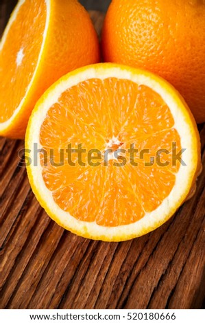 Halves of fresh oranges on a wooden background.