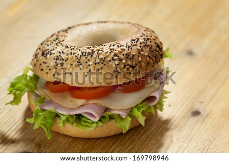 Ham and cheese bagel on a wooden board - stock photo