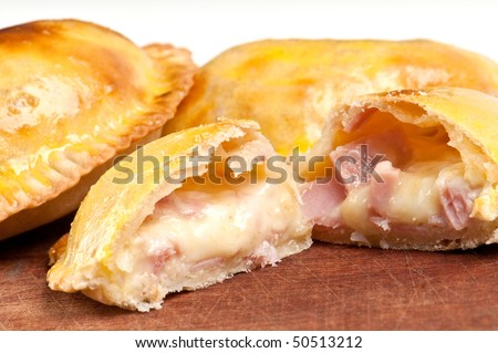 Ham and Cheese Empanada fill close up.  The Empanada is a pastry turnover filled with a variety of savory ingredients and baked or fried. - stock photo