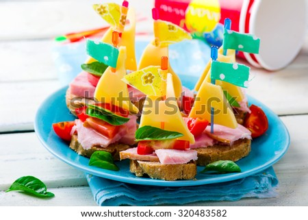 ham and cheese sandwiches in the form of ships for a children's holiday. selective focus - stock photo