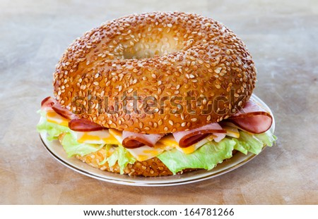 Ham and cheese sesame bagel sandwich on a plate - stock photo