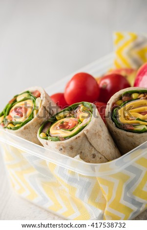 Ham and cheese wraps in lunch box with apple and tomatoes