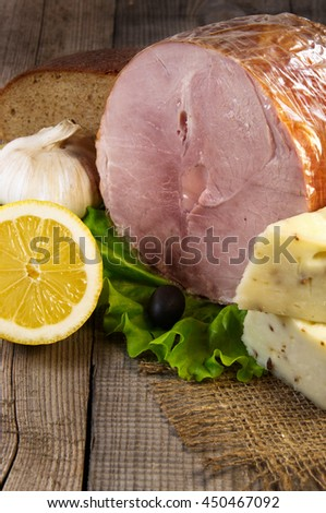 Ham and other snacks on a wooden surface - stock photo