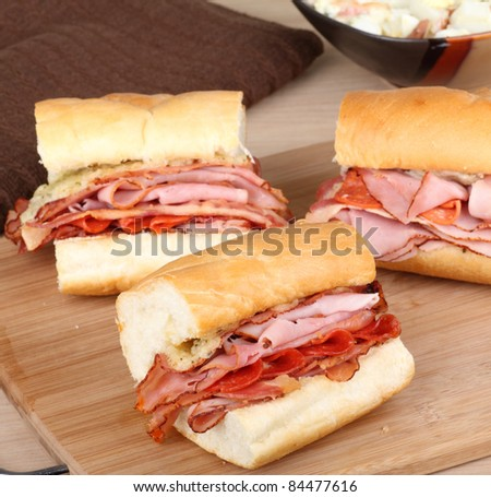 Ham and pepperoni sandwiches on a cutting board