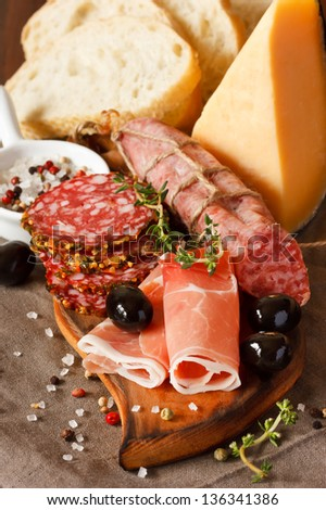 Ham, cheese and variety of salami with olives and spices on wooden board. - stock photo