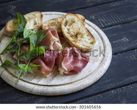 ham, ciabatta, fresh arugula on a wooden Board on a dark surface is a delicious appetizer with wine - stock photo