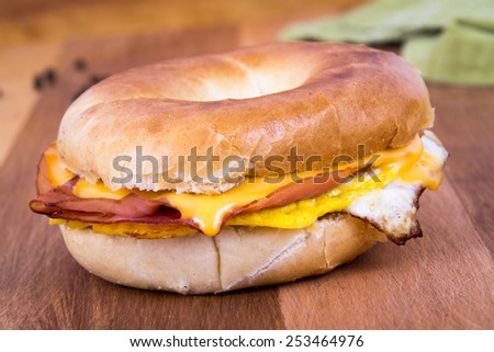 Ham, Egg and Cheese Breakfast Sandwich on a Bagel over a wood table - stock photo