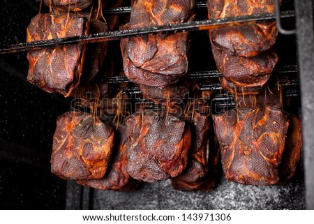 Ham hanging in the smoking house at butcher's shop - stock photo