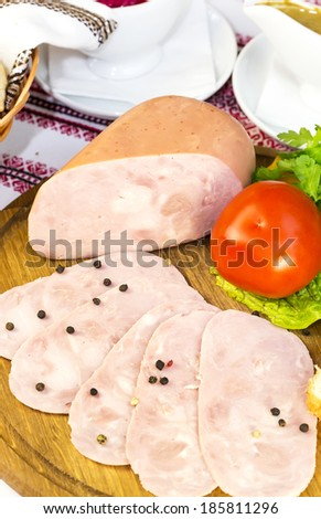 ham on the table in a restaurant with vegetables and sauce - stock photo