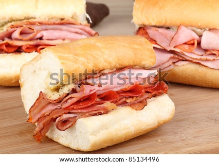 Ham, pepperoni and bacon sandwich on a cutting board - stock photo
