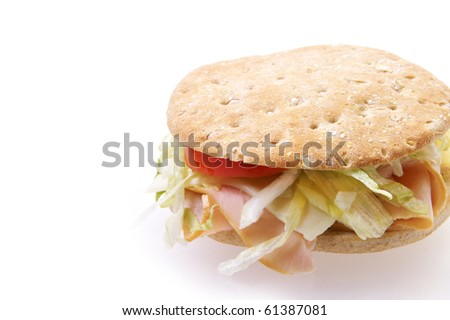 Ham sandwich on multi grain bread with tomato lettuce and mayo on a white background with reflection - stock photo