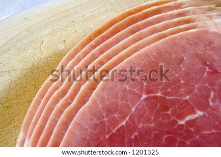 Ham slices on wooden board - stock photo