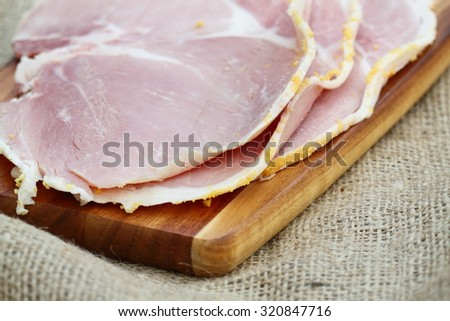 Ham slices wooden chopping board hessian. - stock photo