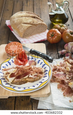 Ham with bread, tomato, garlic and olive oil to prepare the typical Spanish toast - stock photo