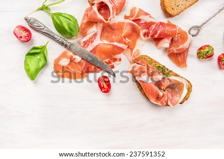 ham with toast,knife, Basil and pesto on white wooden background, top view - stock photo