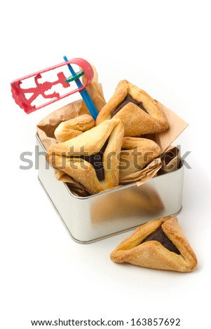 Hamantaschen cookies and grogger forJewish festival of Purim - stock photo