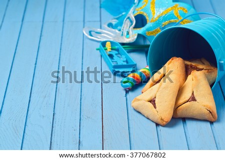 Hamantaschen cookies in bucket for Purim holiday on blue wooden background - stock photo